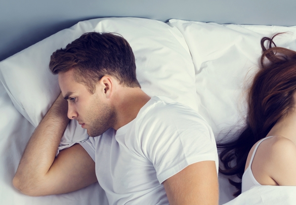 Unhappy Taurus man with his girlfriend on the bed in bedroom