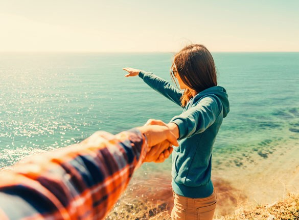 Beautiful young woman holding mans hand and showing him something in distance the sea