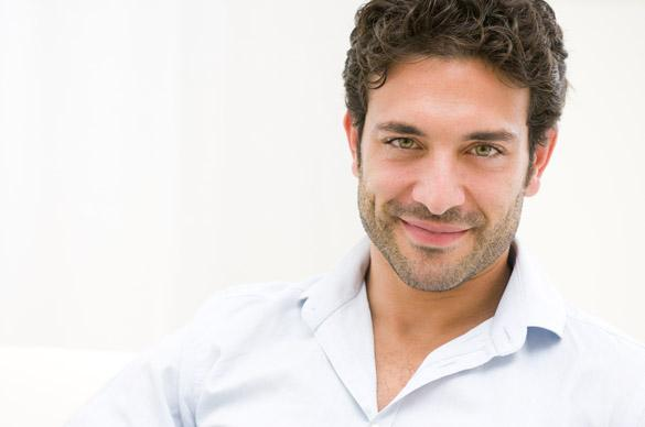 Close up of satisfied smiling Taurus guy looking at camera at home