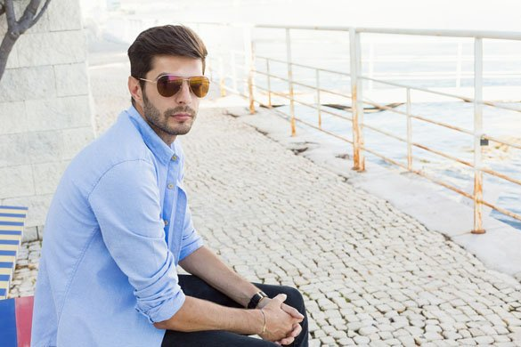 Handsome young man in bluejeans sitting on a bench nearby the sea