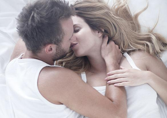 Romantic couple in love kissing in bed