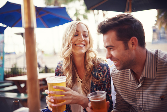 happy couple having a good time drinking beer together at outdoor pub or bar