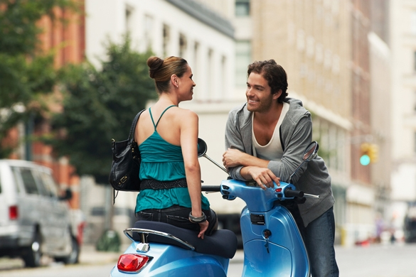 woman-on-moped-talking-to-man-in-street