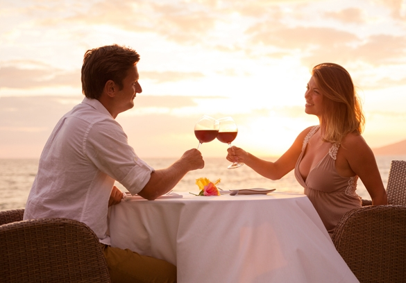 Couple sharing romantic sunset dinner on the beach - how does a taurus man act when in love