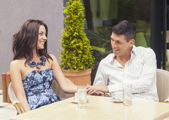 Dating couple talking and relaxing together in a street cafe - what does a Taurus man like to hear
