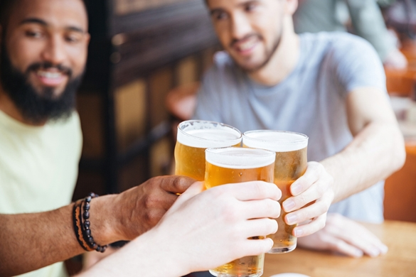 Happy male friends clinking with beer mugs in pub - Negative Traits Of The Taurus Man
