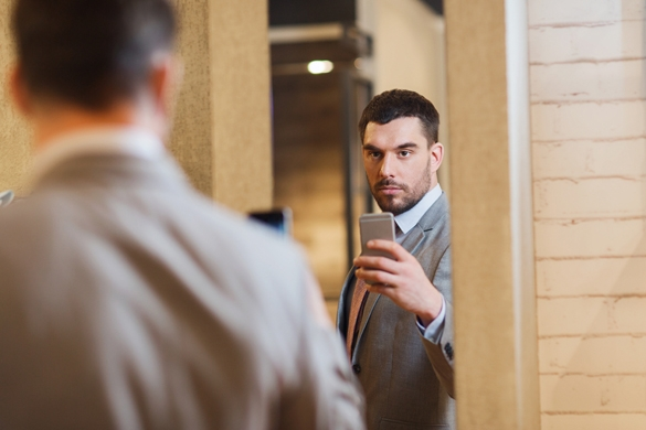 young Taurus man in suit with smartphone taking mirror selfie at clothing store - Negative Traits Of The Taurus Man