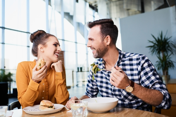 Adult man and woman in casual clothes eating in cafe and smiling to each other - Is A Taurus Guy Interested Or Just Friendly