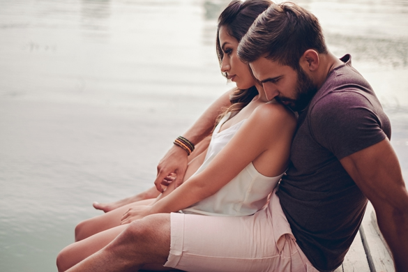 Couple hugging by the river and looking in to water - What Does A Taurus Man Like In An Aquarius Woman