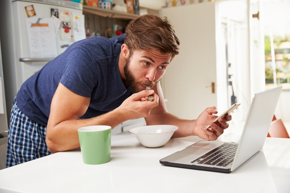 Man Eating Breakfast Whilst Using Mobile Phone And Laptop - Why Are Taurus Men So Secretive