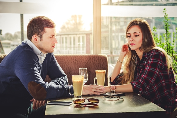 Sad romantic couple holding hands at coffee shop - Taurus Man And Aries Woman Breakup