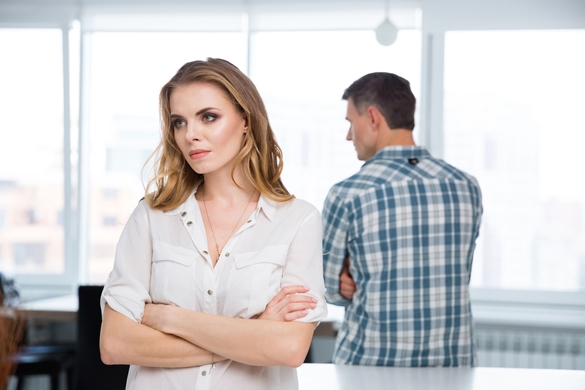 Unhappy woman standing with arms crossed in quarrel with her husband at home - Taurus Man and Capricorn Woman Breakup