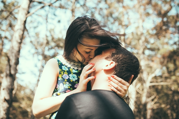 Young couple kissing outdoor in summer sun light - How You Can Tell If A Taurus Man Is Falling For You