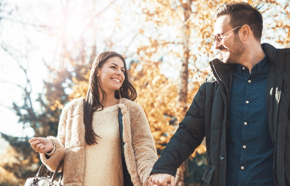 Young embracing loving couple walking through autumn park - How To Seduce A Taurus Man With Words