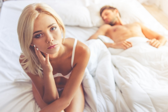 Young woman in white lingerie is sitting on bed and looking at camera while her partner is sleeping - Taurus Man In Bed With Leo Woman
