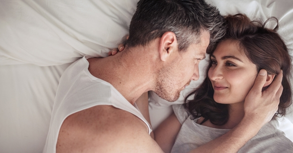 young couple lying in bed together - what does a taurus man like in a libra woman